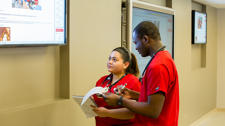 Caldwell University Nursing students taking notes out of the slider form a screen.