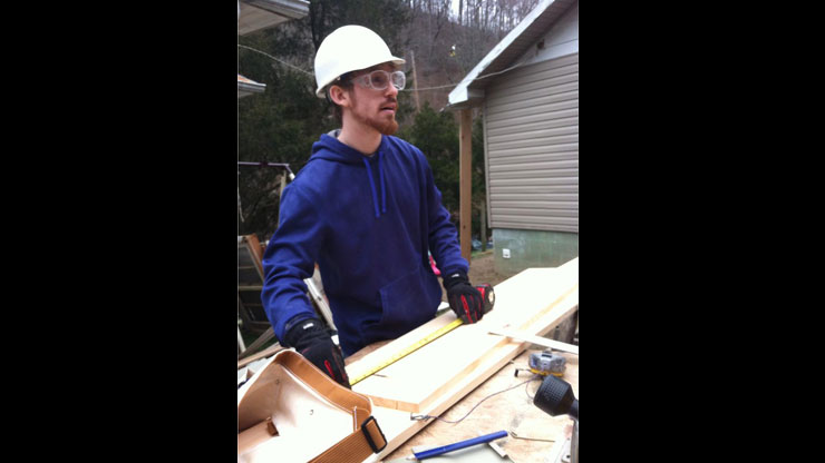A Caldwell Student measuring a flank to repair a house.