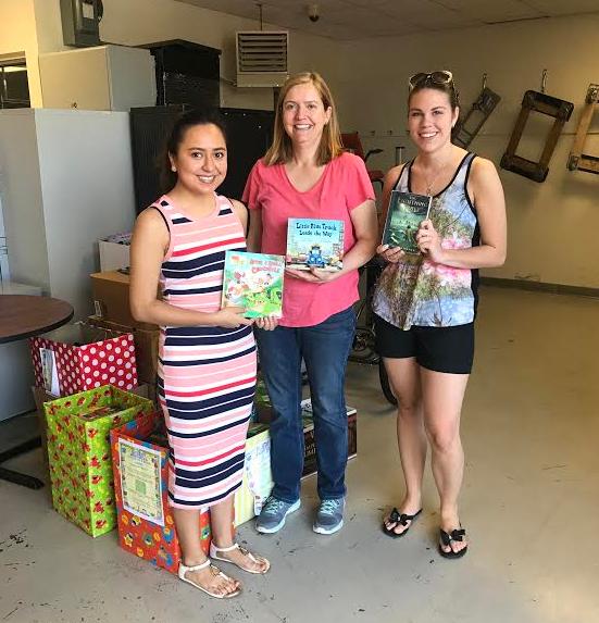 Caldwell Phi Kappa Phi Vice Presidents Katherine Llangari and Alyssa Mol with  Bridge of Books Foundation Volunteer Theresa Jahns.