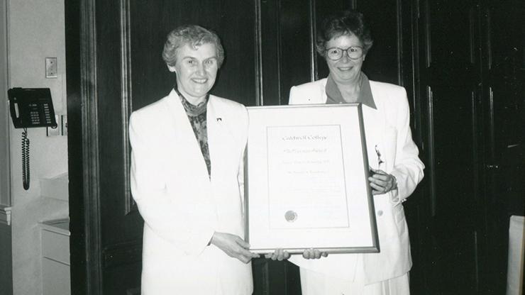 Sister Vivien Jennings holing a certificate.