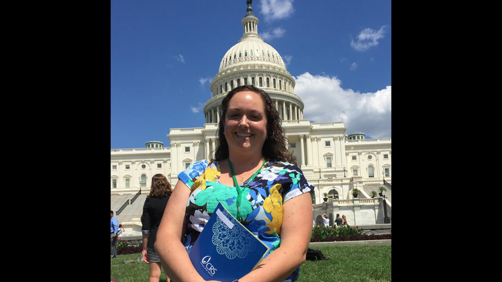 Director of Campus Ministry Colleen O'Brien taking a photo outside a capitol Hill.