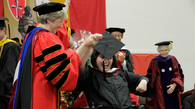 Students lifts her Tassel after receiving her certificate