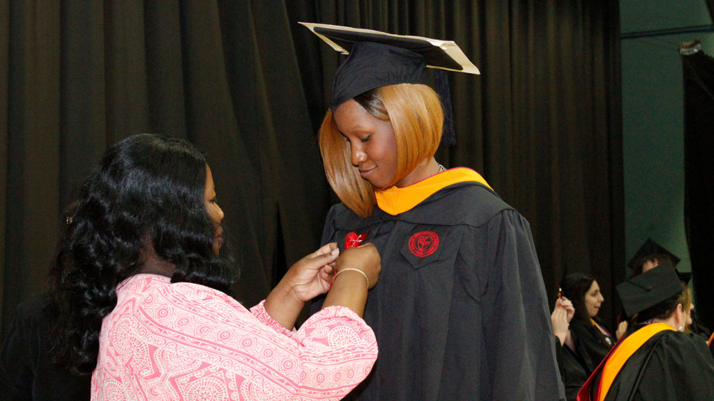 Caldwell University School of Nursing and Public Health graduate senior getting pinned from her mother during annual convocation and professional pinning at May 18.