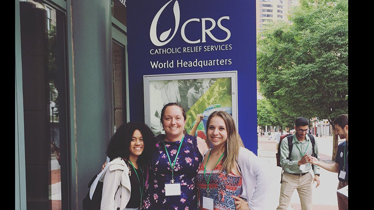 Caldwell University student Guale and Gonzalez along with Director of Campus Ministry Colleen O'Brien taking a photo with the Catholic Relief Services conference banner.