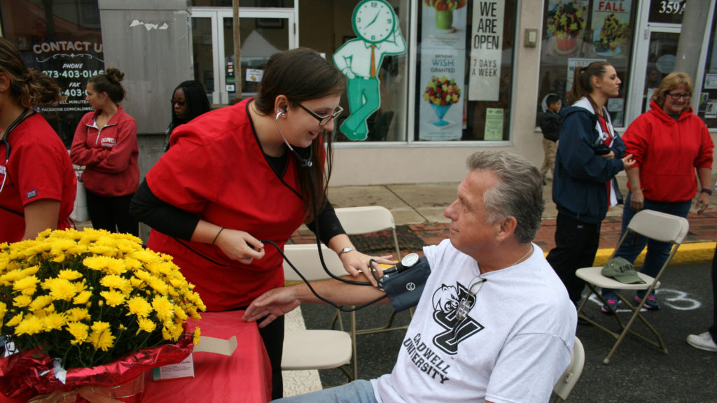 Caldwell University Nursing Student checking Blood Pressure Annual Street Fair 2016