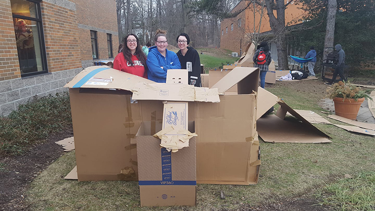 Three Caldwell University students taking part in the Campus Ministry project Boxtown aimed at raising awareness about homelessness.