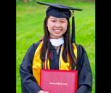 Michelle Eng standing and smiling with her Bachelor of Arts degree in biology.