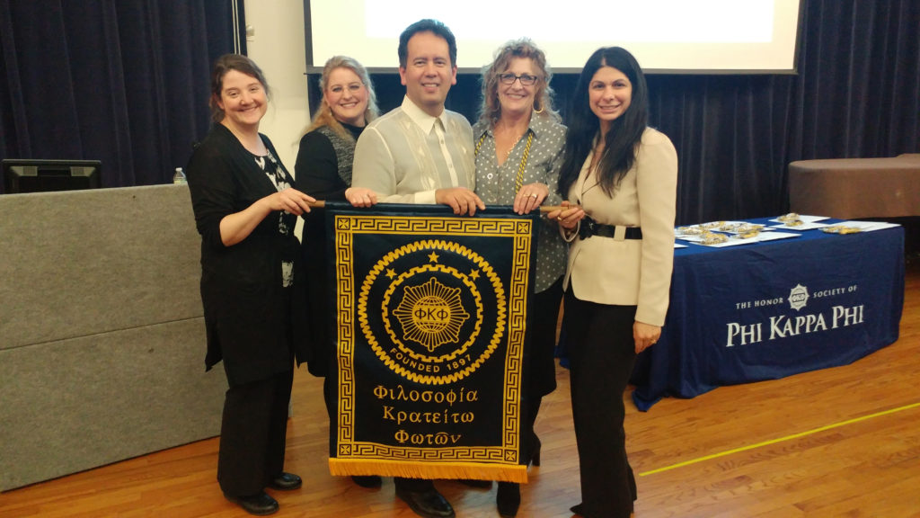 Caldwell University chapter of the honor society Phi Kappa Phi members posing with the banner.