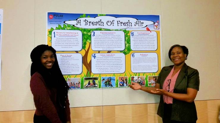 Biology major Shanice Edwards and Director of Caldwell's Educational Opportunity Fund Andrei St. Felix. Edwards is showing her research project for the Premedical Urban Leaders Summer Enrichment Program.