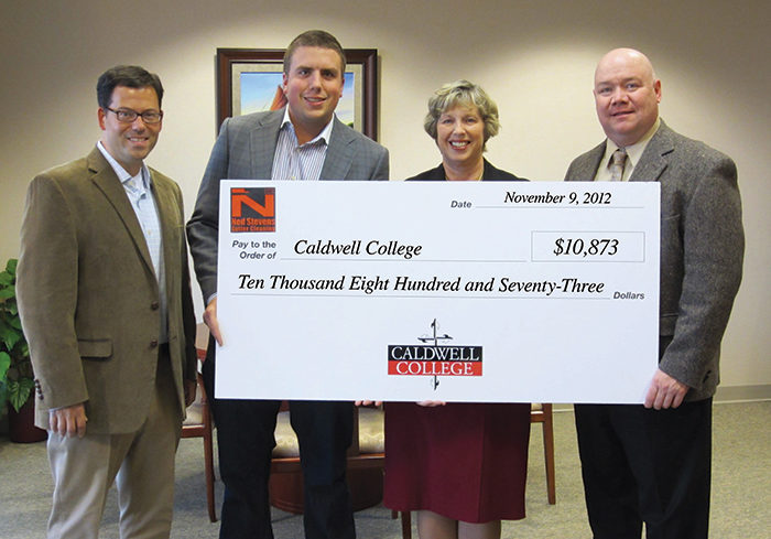 A picture of Ned Stevens Handing the cheque of $10873 to the Caldwell University's president