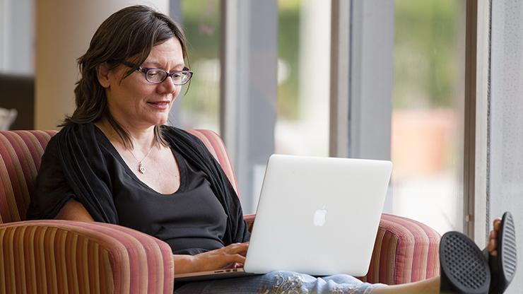 An adult undergraduate student using her laptop