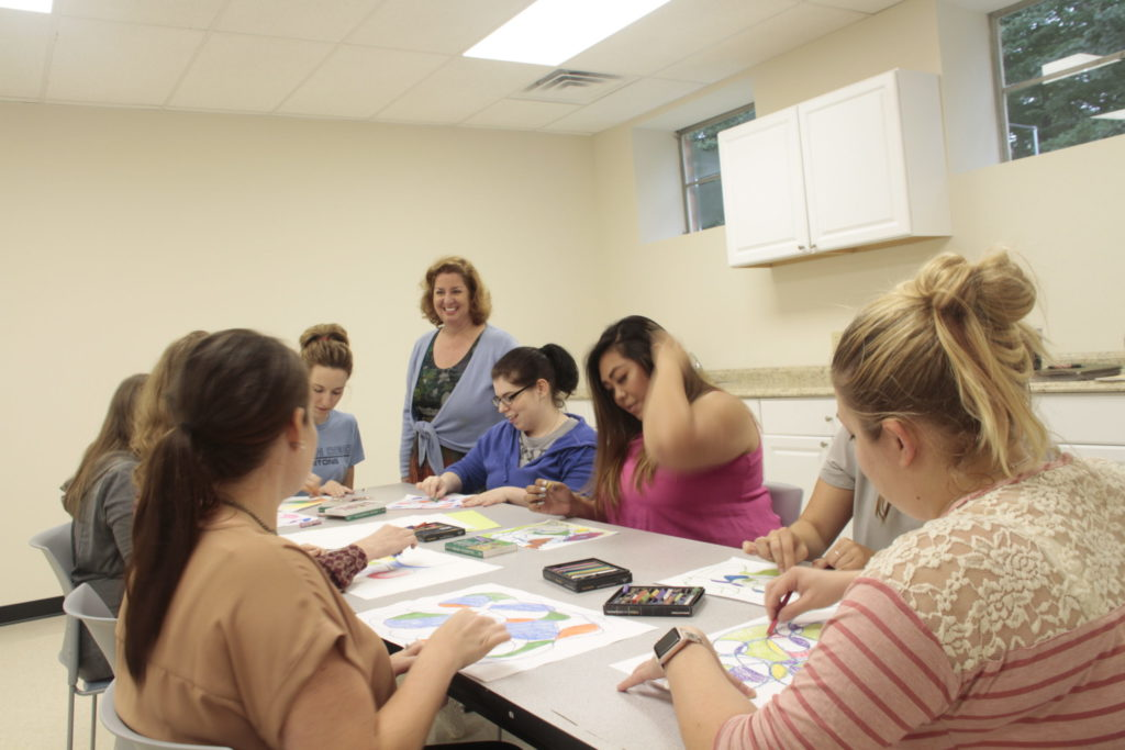 Students working with Dr. Annette Vaccaro in the art therapy center